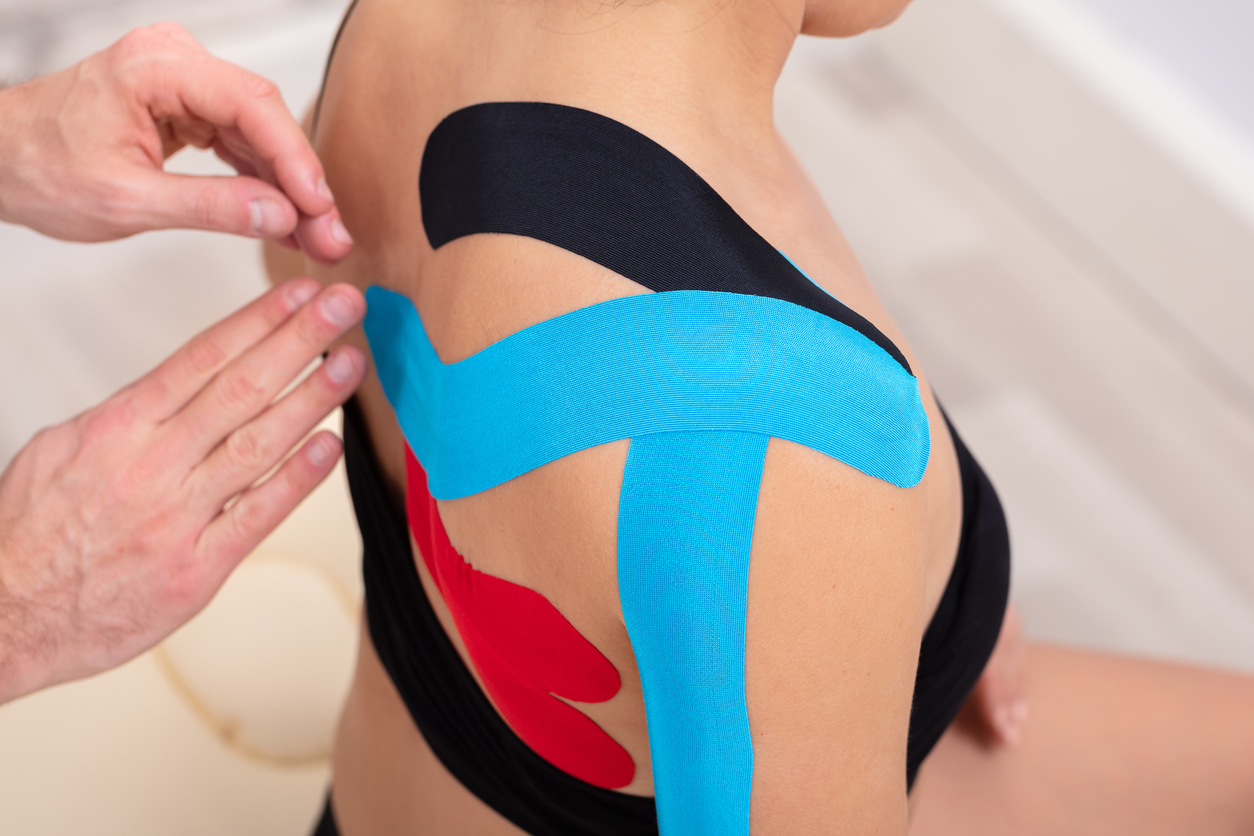 Man Hands Applying Physio Tape On Woman's Shoulder